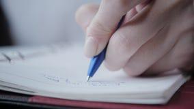 Mano del primer de una mujer que hace notas en un cuaderno Empresaria joven Sitting en cafetería en la tabla de madera En almacen de video