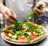 Mano del primer del panadero del cocinero en pizza de fabricación uniforme del blanco en la cocina Imagen de archivo libre de regalías