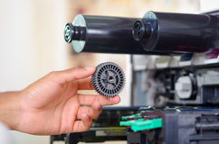 Mano del primer delante de la fotocopiadora abierta durante las reparaciones usando la herramienta del PDA, piezas mecánicas negr Foto de archivo
