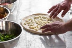 Mano del primer del panadero del cocinero que hace la pizza en la cocina Fotos de archivo libres de regalías