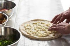 Mano del primer del panadero del cocinero que hace la pizza en la cocina Foto de archivo libre de regalías