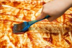 Mano del primer del panadero del cocinero que hace la pizza en la cocina Aplicación de una salsa de tomate El manchar de la salsa imagenes de archivo