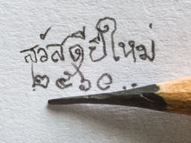 Mano del primer que escribe la Feliz Año Nuevo 2017 en el papel Imagenes de archivo
