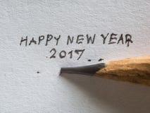 Mano del primer que escribe la Feliz Año Nuevo 2017 en el papel Fotografía de archivo