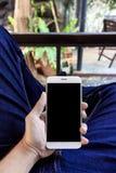 Mano del primer que sostiene smartphone Imagenes de archivo