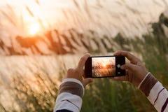 Mano del primer usando el teléfono que toma la foto del paisaje imagen de archivo libre de regalías