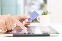 Mano del primer usando la tableta y compras de la tarjeta de crédito foto de archivo