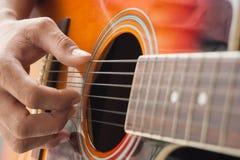 Mano del primo piano che gioca chitarra Fotografie Stock