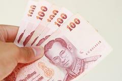 Mano del primo piano con la fattura di cento-baht Immagini Stock