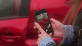 Mano del primo piano dello smartphone della tenuta della donna e prendere foto dell'incidente stradale video d archivio