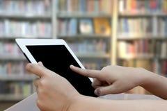 Mano del primo piano facendo uso della compressa digitale sul fondo blured delle biblioteche Fotografia Stock Libera da Diritti