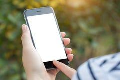 Mano del primo piano facendo uso dello schermo di bianco del telefono Fotografia Stock Libera da Diritti