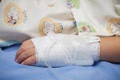 Mano del primo piano del malato del bambino con il tubo dell'acqua salata sul letto Immagine Stock