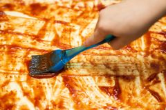 Mano del primo piano del panettiere del cuoco unico che produce pizza alla cucina Applicazione della salsa al pomodoro Ungitura d immagini stock