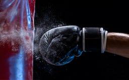 Mano del primo piano del pugile al momento di impatto sul punching ball sopra fondo nero fotografie stock