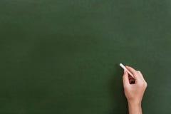 Mano del profesor o del estudiante que sostiene un palillo de la tiza Imagen de archivo