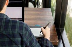 Mano del progettista dello studente che attinge il cuscinetto di topo della penna con il computer portatile Fotografie Stock Libere da Diritti
