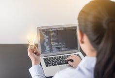 Mano del programador de la mujer joven que sostiene la bombilla, manos de la mujer que cifran y que programan en el ordenador por fotos de archivo