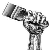Mano del puño del grabar en madera de la propaganda que sostiene la brocha Fotografía de archivo