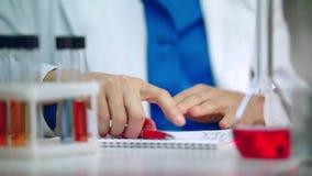 Mano del químico usando la PC de la tableta Tableta del movimiento en sentido vertical de la mano de la mujer del químico almacen de metraje de vídeo