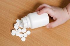 Mano del ` s del bambino che tocca una bottiglia delle pillole Immagine Stock Libera da Diritti