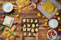 Mano del ` s del bambino con i biscotti e gli ingredienti di Sugar Easter per bakin Fotografie Stock