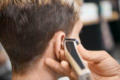 Mano del ` s del barbiere facendo uso della tosatrice, facente nuovo taglio di capelli per il cliente fotografia stock libera da diritti