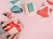 Mano del ` s de la muchacha de la belleza con el control del paño del invierno el ingenio de la caja de regalo del oro Fotos de archivo libres de regalías