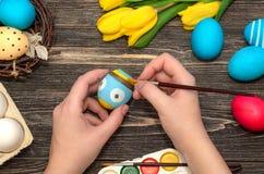 Mano del ` s de la muchacha que pinta los huevos de Pascua Foto de archivo libre de regalías