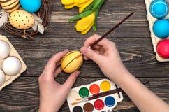 Mano del ` s de la muchacha que pinta los huevos de Pascua Foto de archivo