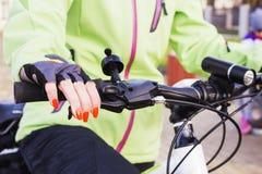 Mano del ` s de la mujer con el esmalte de uñas brillante en la rueda de bicicleta Imagen de archivo libre de regalías