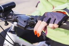 Mano del ` s de la mujer con el esmalte de uñas brillante en la rueda de bicicleta Foto de archivo libre de regalías