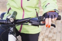 Mano del ` s de la mujer con el esmalte de uñas brillante en la rueda de bicicleta Fotografía de archivo libre de regalías