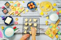 Mano del ` s de la mujer con las galletas y los ingredientes de Sugar Easter para el bakin Imágenes de archivo libres de regalías