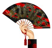 Mano del ` s de la mujer con una fan china negra con grago decorativo del oro stock de ilustración