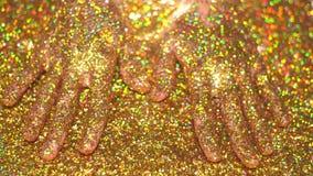 Mano del ` s de la mujer en brillo de oro Fotografía de archivo