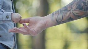 Mano del ` s de la mujer en tacto del tatuaje la mano del ` s del niño metrajes