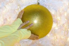 Mano del ` s de la mujer para coger la bola de Navidad Imagen de archivo libre de regalías