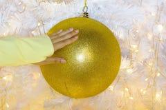 Mano del ` s de la mujer para coger la bola de Navidad Foto de archivo libre de regalías