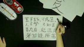 Mano del ` s de la mujer que escribe caligrafía china Mano femenina que lleva a cabo caracteres chinos de un cepillo de escritura almacen de video