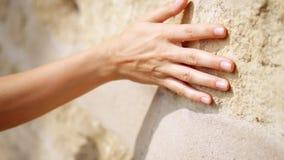 Mano del ` s de la mujer que se mueve sobre la pared de piedra vieja Desplazamiento adelante Tacto sensual Superficie de piedra d almacen de video
