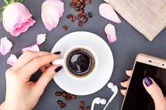 Mano del ` s de la mujer que sostiene la taza de café y de smartphone imagen de archivo