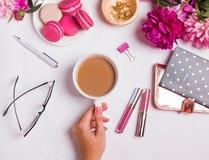 Mano del ` s de la mujer que sostiene la taza con café en la tabla con diferente Fotografía de archivo