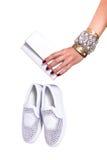 Mano del ` s de la mujer que sostiene un embrague del cuero blanco y zapatos blancos con los diamantes artificiales Fotografía de archivo libre de regalías