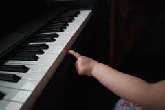 Mano del ` s de la niña al lado del piano Un pequeño finger intenta pulsar las teclas Ninguna cara Cierre para arriba fotografía de archivo