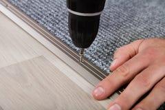Mano del ` s de la persona que instala la alfombra en piso imagen de archivo libre de regalías
