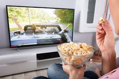 Mano del ` s de la persona que sostiene las palomitas mientras que la película juega en la televisión foto de archivo