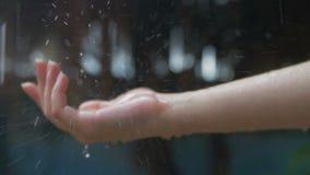 Mano del ` s de las mujeres cubierta en gotitas de las fuertes lluvias almacen de video