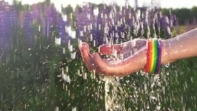 Mano del ` s de las mujeres en la lluvia con el simbolismo de la pulsera de LGBT, concepto almacen de metraje de vídeo
