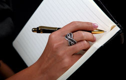 Mano del ` s de las mujeres escribir-en el cuaderno Foto de archivo libre de regalías